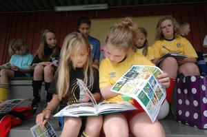 Sanna Hälsing och Ebba Westling bläddrar i en av böckerna som barnbibliotekarien Anette Helgesson haft med sig till fotbollsskolan.