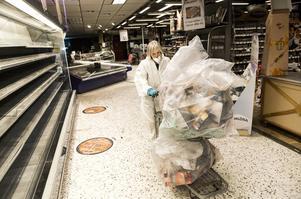 Britt-Marie Forsberg, till vardags kassörska, hjälper till att forsla bort kasserad mat.