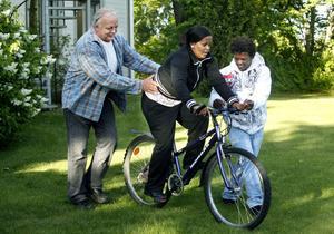 Stanley Lenell hjälper Nigsty Semere att hålla balansen när hon lär sig cykla. Luwan Andemichel ger också lite stöd.