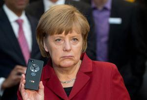 En märkbart nedstämd Angela Merkel håller symboliskt upp sin mobil inför fotograferna, telefonen som USA avlyssnat, vilket skapat en allvarlig politisk turbulens