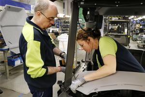 Stefan Larsson och Jessica Faraj monterar fast en instrumentpanel. Stefan Larsson har varit mer än 40 år i företaget.