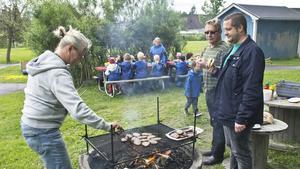 Socialdemokraterna Ola Wahlsten och Mikael Björlestrand imponerades av förskolläraren Karin Dahlströms effektiva sätt att grilla hamburgare.