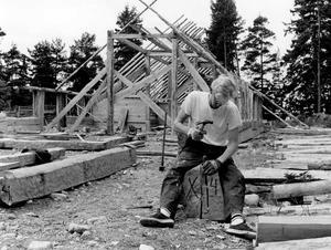 13 juni 1990. Arkitekturstuderande Stefan Forsberg från Lund har anslutit sig till vikingabygget på Vallby friluftsmuseum. Här håller han på att hugga ut en not i en av de stockar som ska ligga i grunden.