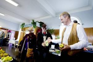 ÄPPELUTSTÄLLNING. Sylve Rolandsson som höll i gårdagens äppelutställning på Stationshuset i Storvik får här ta emot en påse äpplen av den lokala konstnären Tord Larsson och hans sällskap, Åsa Olsson.