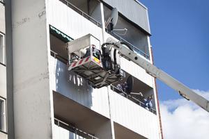 Det blev fullt pådrag efter larmet om att det vällde rök ur en bostad på Norra Köpmangatan. Här är skyliften upp på femte våningen för att släcka den glödande fimpen.