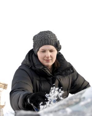 Madelene Larsson skrapar bilrutorna för att köra till jobbet.