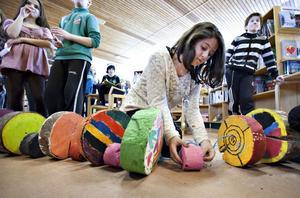 """SAMMANFOGAR DELARNA. Elvaåriga Natalie Abbaszadeh målade sin träbit i glada färger, rosa och blått. Här binder hon ihop några av delarna femteklassarna har målat under invigningen av utställningen """"Bygga broar"""" som visas på Sätra bibliotek."""