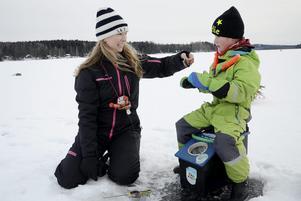 Fångst. Charlie Persson har fått en fisk på kroken, igen. Här nappar det som bara den. Mamma Gabriella Persson hjälper till att plocka av fångsten från kroken.
