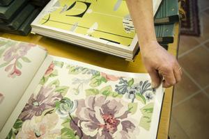 Vissa tillverkare tar fram tyger som matchar tapeterna. Sanderssons har en sådan kollektion, bland annat dessa blommor i milda färger. I katalogen bredvid skymtar ett grafiskt mönster inspirerat av 1960-talet.