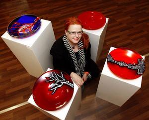 Mari Zidén bland några av sina färgsprakande glasfat.