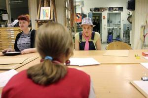Moa Östman (ESBIL12) och hennes lillasyster Wilma Östman gör teckningar av varandra under bordet, utan att få titta. Till vänster sitter den tidigare esteteleven Jolin Skoglund.