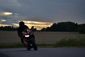 En höstvacker kvällshimmel tillsammans med åkrar mogna för skörd och en sista åktur med motorcykeln innan det är dags att förbereda sig för vinter. Allt på samma bild.