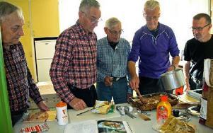 Matlagningsgruppen samlade kring Lennart Andersson som lägger sista handen på lasagnen. De övriga heter Roger Larsén, Karl-Ivar Gustavsson, Anders Johansson och Sven-Erik Karlsson. Foto: Eva Högkvist