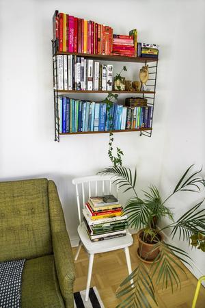Stringhyllan är ett arvegods och i den har Lina Lindbladh placerat böckerna i färgordning för en harmonisk känsla. På stolen nedanför har hon böcker om ätbara växter nära till hands, många av dem är köpta second hand.