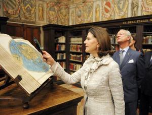 ITALIEN. Kungaparet besöker Archiginnasio den äldsta fakulteten på Universitet i Bologna med ett i dag fortfarande fungerande bibliotek. Drottning granskar med förstoringsglas en gammal karta över Skandinavien.