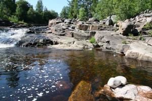 Man solar på klipporna och badar i det forsande vattnet.