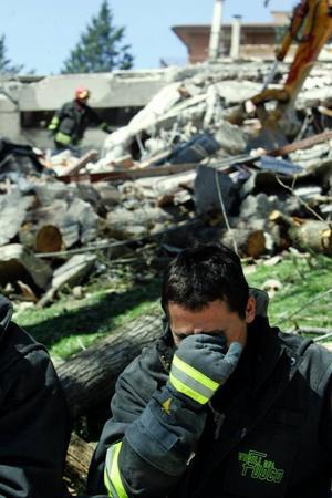 En brandman sitter framför ett raserat hus i staden L'Aquila. Foto: Scanpix