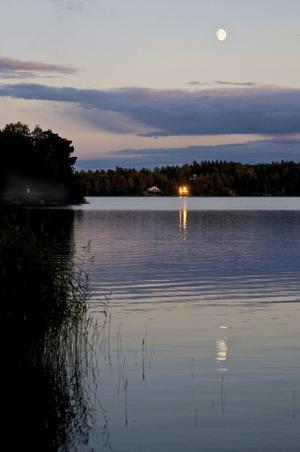 Under endast några minuter varje kväll står solen så att den reflekteras i fönstren på huset tvärs över sjön. Det är det som gör att nästan ser ut som att huset brinner.