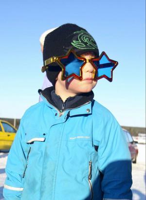I solsken och vintervitt landskap samlades Sikåsborna när byns sparktävling skulle avgöras. Ett 70-tal personer samlades för att se när barn och vuxna tävlade.Olle Stjernström är snygg i sina nya solglasögon. Alla barn som var med i sparktävlingen fick förstås fina priser.