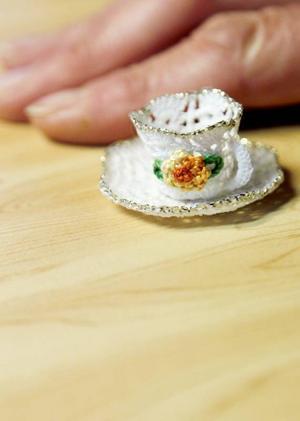 Kaffekoppen i miniatyr är virkat i vit sytråd och sedan stärkt med sockervatten. Miriam Jönsson räds inte pilliga projekt.