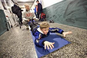 """UPPVÄRMNING I KORRIDOREN. Naprapaten Lars Wikström tränar styrka och rörlighet med William varje bandyträning. """"William har utvecklats mycket under sex månader som vi har tränat. När vi började var styrkan i benen som hos en treåring, nu är den som hos en sjuåring. Det kan bara bli bättre"""", säger Lars."""