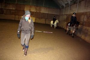 Jenny Grahn håller sig hela tiden i rörelse i ridhuset, för att följa ryttarna och deras hästar och även för att själv hålla värmen.