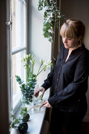 Stylisten Jenny Martinsson pyntar sitt fönster med vaser, blommor och ett älghorn. Personligt och vackert.