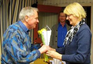 Klubbens kassör Eva Persson överräcker blommor till avgående Gert Doll. I bakgrunden ses nye ordföranden Mats Hult.