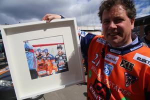 Konstnären Carl Posse med en av sina tavlor, som klubben auktionerar ut, med motiv hämtade från bandyfotografen Kenta Jönssons bilder. Just den här blev Årets Bandybild.