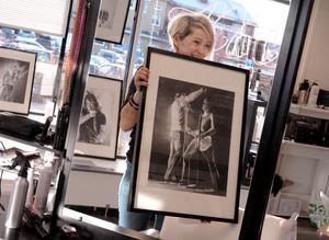 OLJA. Senaste Takida-tavlan är målad med olja och föreställer gitarristen Tomas Wallin. Konstnären Marie Åkerlund och Tomas Wallin hänger upp tavlan.