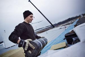 2: Arbete vid byggmästers stora bygge på Hacksta angående att det är lättare att arbete när det är mild vinter. Företaget Svetak:s Alexander Höök bär takpapp på det 6000 kvm stora taket.
