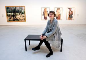 Karin Levander. I bakgrunden syns verk av fotokonstnärerna Annika von Hausswolff och Cecilia Edefalk.