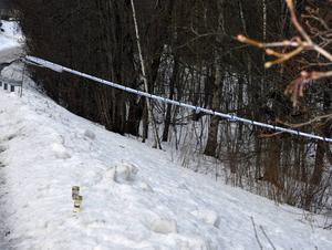 Ljus med sista hälsningar till den döde 45-åringen står vid avspärrningarna på Skönviksvägen.