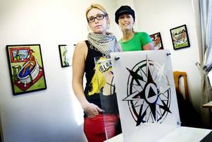 Riktning Hofors. Två av konstnärerna som samlats kring temat tecken är Johanna Fröjd (som gjort kompassrosen) och Veroniqa Perzon vars bilder syns på väggen bakom.Foto: David Holmqvist