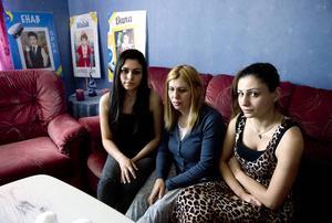 Döttrarna Dana och Malak Alayan sitter på var sida av mamma Faten.