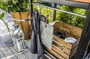 På uteplatsen står en grill och väntar på att användas alla varma sommardagar. Smart förvaring i träbackar som skapar en rustik känsla och som döljer trista matlagninstillbehör. Fiffiga krokar hänger på räcket och är perfekt till att både lite snitsigt hänga upp förklädet eller kanske låta kökshandduken torka i solen...