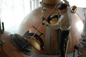 Det här är en snarlik variant av fotot som är förlaga till frimärket. Bilderna av Tommy Jansson som spolar rent en av pannorna i destilleriet hos Mackmyra whisky togs för ungefär tre år sedan och ligger bland annat på företagets hemsida.