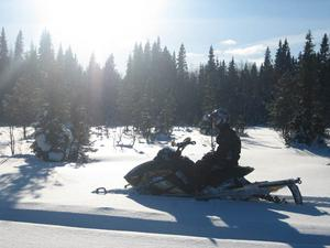 Andreas Sjöström på sin skoter tittar bort mot solen å drömmer sig bort. Foto: Fredrik Sjöström