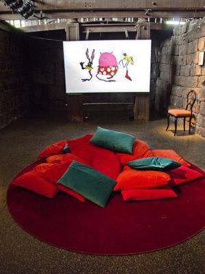 Tecknaren Stina Wirséns avdelning i utställningen lockar besökarna att slå sig ned i kuddberget. Här finns möjlighet att följa konstnärens väg från idé, första skisser till färdig film.