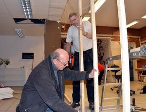 Ove Svedin och Urban Jansson reglar upp för väggen som ska skilja verkstäderna och butiken.