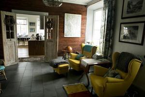 Det gamla kapprummet har blivit sällskapsrum med fina fåtöljer. I öppningen in till  köket sitter det som tidigare var ytterdörrar.