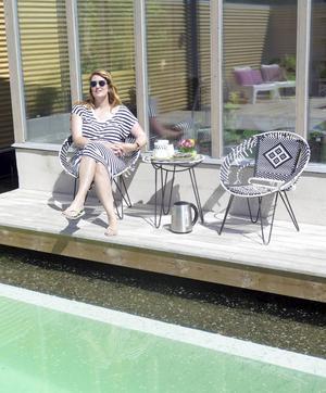 Wilma njuter i solen. I framkant på bilden syns övergången mellan baddel och pool där vattnet cirkulerar genom grusbädden.