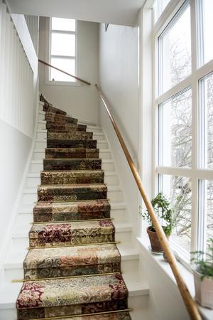 En gångmatta med trappstänger i mässing är en flirt med husets gamla stil.