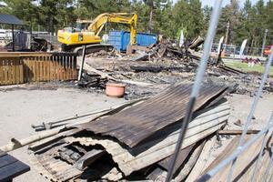 Resterna efter restaurangbranden rensas bort, ett arbete som startade på torsdagen.
