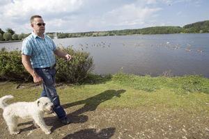 – Det känns inget vidare att promenera runt Lillfjärden, när man måste kliva i all fågelskit, säger Benny Parspark med hunden Leija.foto: lars sundin