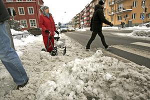 Urdåligt väglag vid övergångsstället i korsningen Trädgårdsgatan/Nygatan, förra veckan. Lika illa var det på trottoaren där varken skidor eller sparkstötting fungerat i slasket. Alfhild Aveborn ska försöka ta sig över gatan med sin rullator.