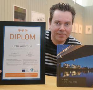 EU-projektet Trästad 2012 har avslutats och Anders Rosell visar det diplom och den bok Orsa kommun tilldelats för sin medverkan.