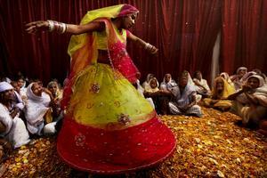 Indiska änkor ser på traditionell dans under färgfestivalen.