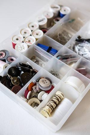En plastlåda med fack och lock (finns på bland annat byggvaruhus) är perfekt för alla sytillbehör. Spara extra knappar som följer med nya plagg i ett särskilt fack.