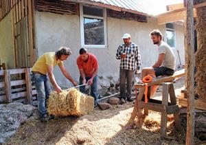 Gandee Apzeed, Feras Saad Alah, Mautz Lebbad och Allan Stewart mäter och sågar upp halmbalar som ska bli husets tak.
